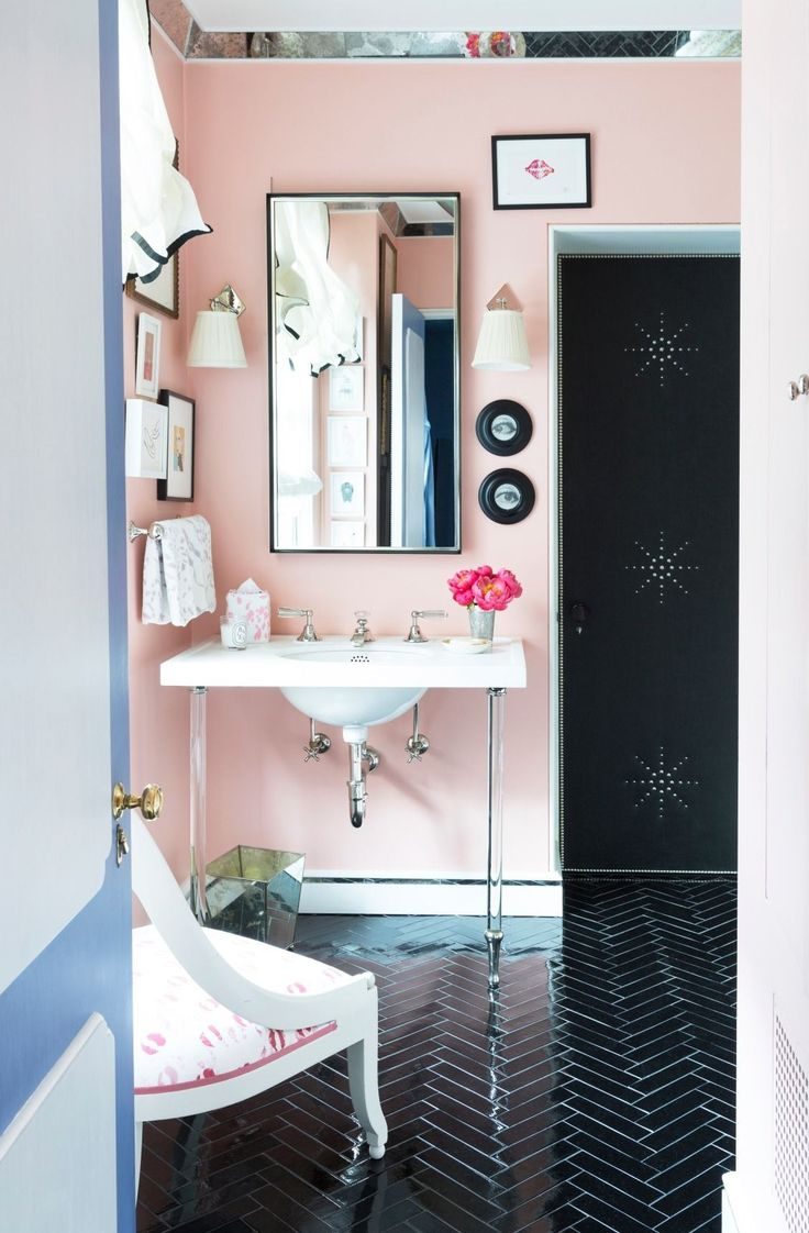 A custom mixed paint of Ralph Lauren's Persian Sunset is the perfect pink to offset the modern acrylic legs of the console sink and the dramatic black tiled parquet floors.