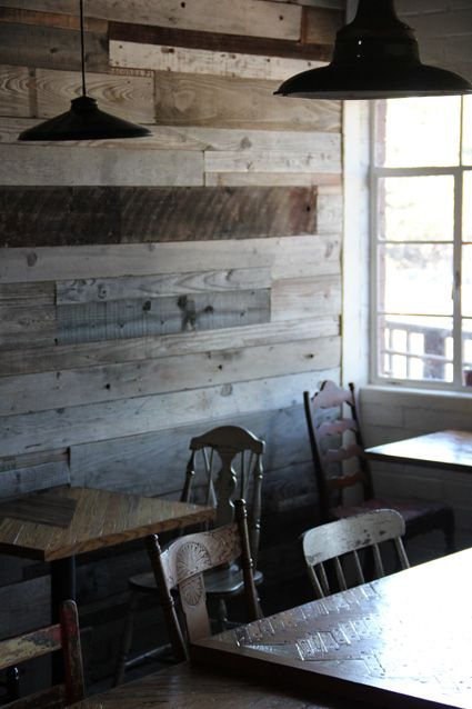 reclaimed wood wall, mismatched wooden chairs and rustic tables ...