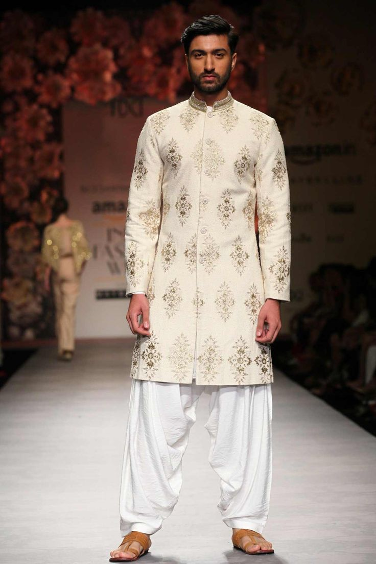 Beige classic appliqué and crystal sherwani with white patiala available only at Pernia's Pop Up Shop.