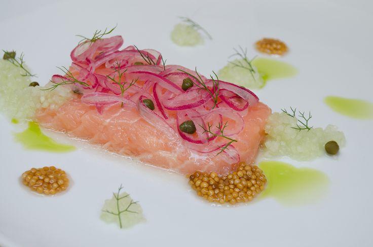salmón curado al vacío, semillas de mostaza encurtida, cebolla roja encurtida, pepino, alcaparra, tostadas con crema, cebollina y rábano picante  Foto: Pablo Henao