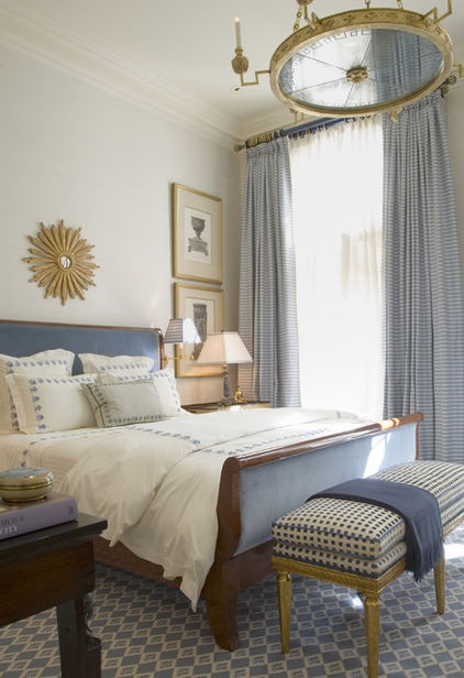 Retrofit a standard sleigh bed with fabric panels. A touch of soft blue in the headboard and footboard helps to break up the heavy wood and preserve the room's subdued feel.