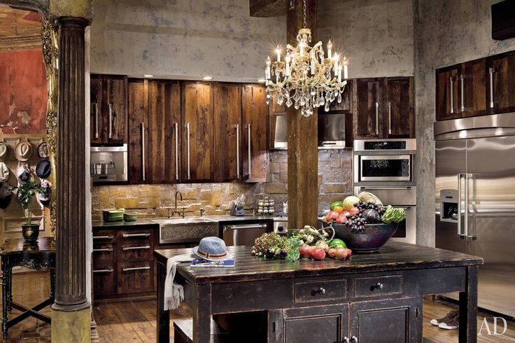 """With its mottled walls, weathered surfaces, and crystal chandelier, Gerard Butler's kitchen looks at first glance like it belongs in a medieval castle—until you notice the modern appliances. The actor described his loft, located in a converted manufacturing warehouse in New York's Chelsea neighborhood, as a """"bohemian old-world rustic château with a taste of baroque."""" The kitchen's cabinetry and backsplash were fashioned from leftover flooring materials. (May 2010)"""