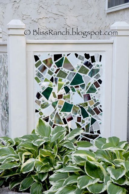 A few years ago I was sitting on the patio looking around and I wondered what I could do to hide the big 'ol ugly air conditioning unit.  We had a pile of old deck posts, so Brawn whipped me up a form with two panels and I smashed some china and stained glass along with some mirror and made a big mosaic to hide it.