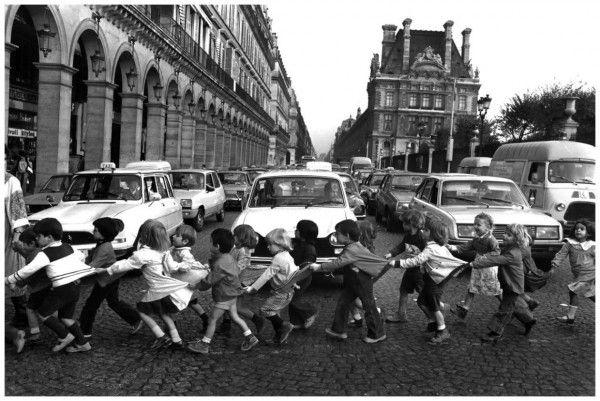 """Robert Doisneau - """"I grembiulini di Rue de Rivoli"""" (1978) - Appena fuori dal Louvre, un gruppo di scolaretti ferma il traffico. L'allegria e l'innocenza dei bambini rappresentano, per l'autore,  il simbolico potere che essi hanno di poter far fronte a tutto, anche al correre dei tempi moderni."""