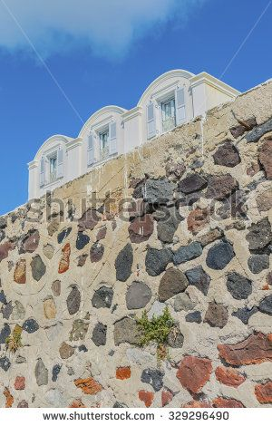 Traditional Greek houses with domed roofs above stone wall at Santorini island..Cyclades.Greece.Europe.