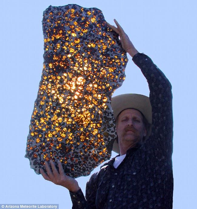 Fukang Meteorite: Discovered in 2000, in the Gobi Desert in China's Xinjiang Province.     It is a pallasite; a type of iron meteorite, quite rare, made out of large olivine crystals in an iron-nickel matrix. Olivine is a magnesium iron silicate, quite common in our planet's subsurface, but which weathers fast when exposed to the surface.   Pallasites are extremely rare, (only about 1% of all meteorites). Slices from the Fukang mass, as in this photo, are reminiscent of stained glass…