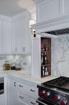 Shaker kitchen boasts a paneled vent hood over built-in hidden spice shelves lit by a nickel sconce alongside an Ann Sacks Beau Monde Grace tile backsplash above a Wolf Range.