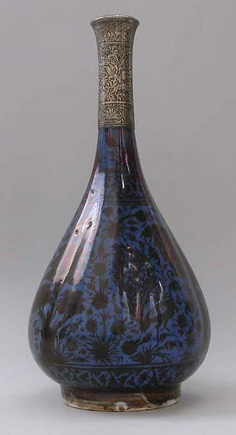 Bottle Depicting a Peacock in Foliage Object Name: Bottle Date: 17th century Geography: Iran Culture: Islamic Medium: Stonepaste; luster-painted on blue glaze under transparent glaze; silver mount Dimensions: H. 13 1/2 in.