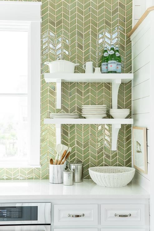Coastal Living Showhouse - White and green kitchen features white cabinets paired with white quartz countertops and a ceiling height green herringbone tiled backsplash lined with stacked white shelves with corbels.