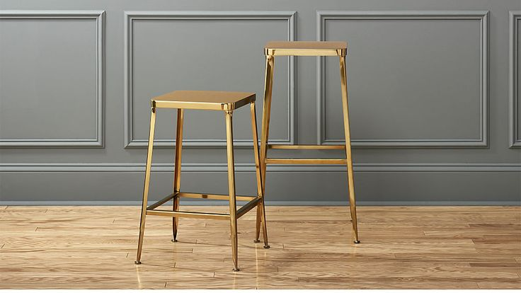 """Shop flint gold bar stools. (24"""" $189.00) Factory-inspired stool parks square at the bar in flint steel with a glam gold finish and exposed welding.  Legs flare refined, love those little capped feet.  Each a handcrafted original."""