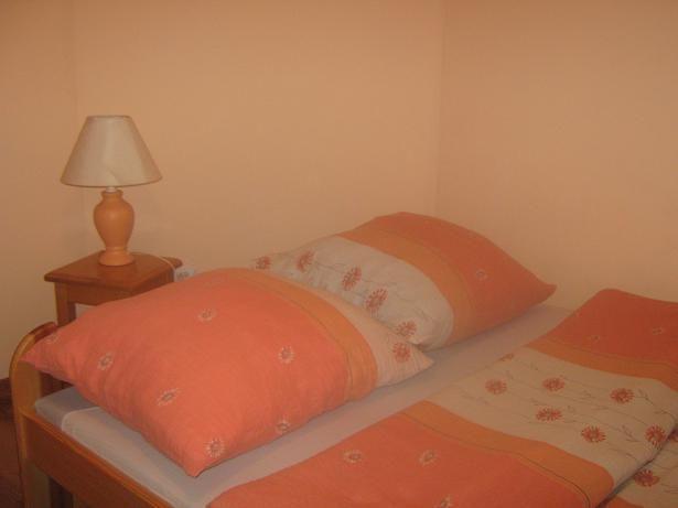 Łóżko w pokoju dwuosobowym na poddaszu .