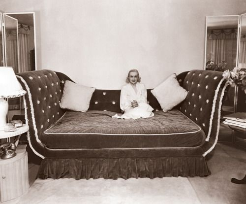 Carole Lombard sitting on her amazing bed.