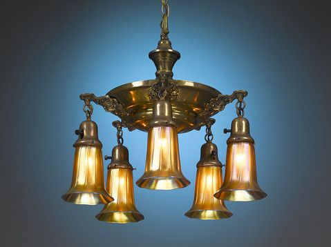 A beautiful iridescent golden glow is emitted from the art glass shades of this outstanding arts and crafts era chandelier by quezal art glass and