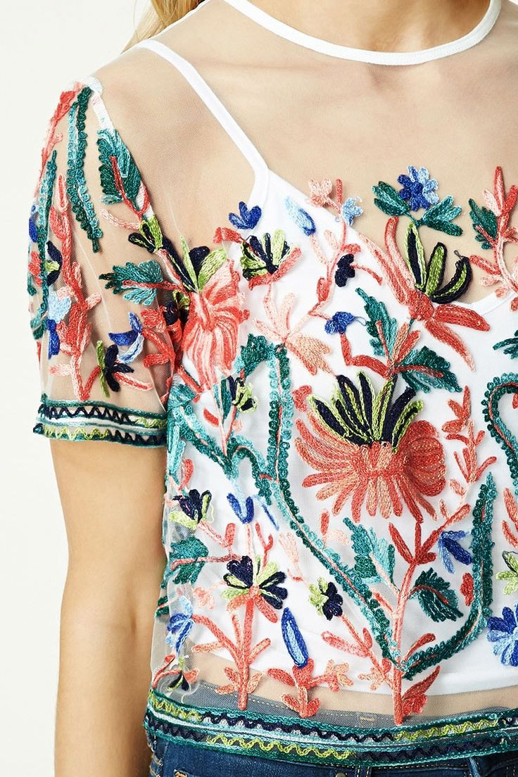 A semi-cropped sheer mesh top featuring a floral and foliage embroidery, geo embroidered trim, a round neckline, short sleeves, a back button closure with a keyhole cutout, and a boxy silhouette.