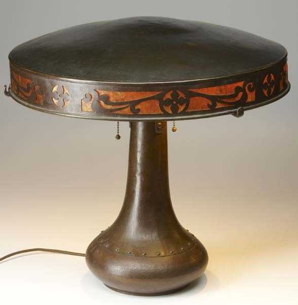 """DIRK VAN ERP:  Unusual wrought copper and mica lamp with a broad, flat shade and a mica-backed, reticulated copper band of stylized floral design, over a three-socket riveted base with squat bottom, c. 1915. Excellent original patina and mica, sockets, and pulls. Minor blemishes to patina on top of shade, excellent original condition. Windmill stamp, not entirely legible, on right side. 18"""" x 20"""""""
