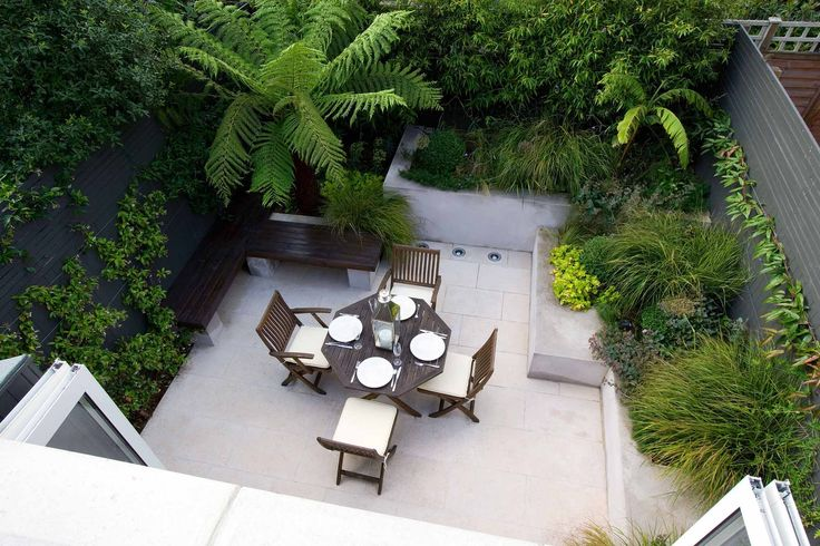 SMALL TOWN GARDEN DESIGNED BY CHARLOTTE ROWE - VIEW LOOKING DOWN ONTO GARDEN WITH PATIO WITH RAISED BEDS, DICKSONIA ANTARCTICA AND TABLE AND CHAIRS. A PLACE TO SIT
