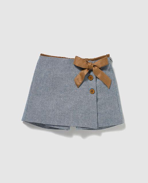 Short tipo falda en azul con lazo en color marrón a contraste. Cierre con botones en un lateral.