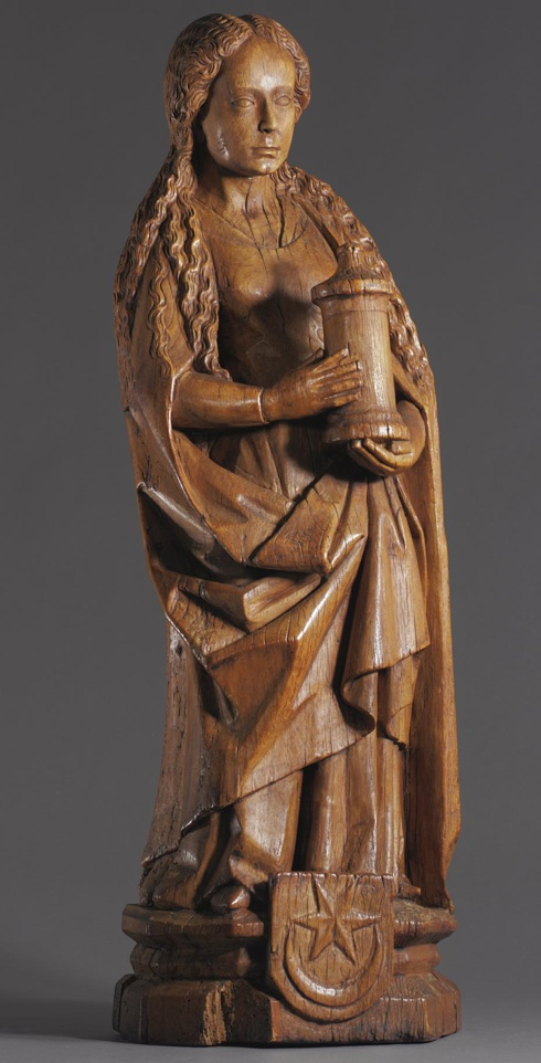 A NETHERLANDISH OAK FIGURE OF ST. BARBARA  LATE 15TH CENTURY  her long tresses falling over her cloak, holding the tower in her hands, a shield with a star and crescent moon emblazoned on the hexagonal base.  height 38 3/8 in.  97.4cm