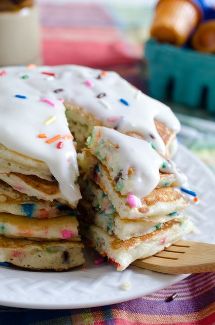 Birthday Cake Pancakes  1 1/2 cups all-purpose flour  1 cup yellow cake mix (homemade or the box kind)  1 Tablespoon sugar  1 teaspoon baking powder  1/2 teaspoon baking soda  1/4 teaspoon salt  2 eggs  1 1/2 cups buttermilk  1/2 cup milk  2 Tablespoons butter, melted  1 teaspoon vanilla extract  1/3 cup (1.75 oz bottle) sprinkles  For the icing (optional):  Whipping cream  Powdered sugar