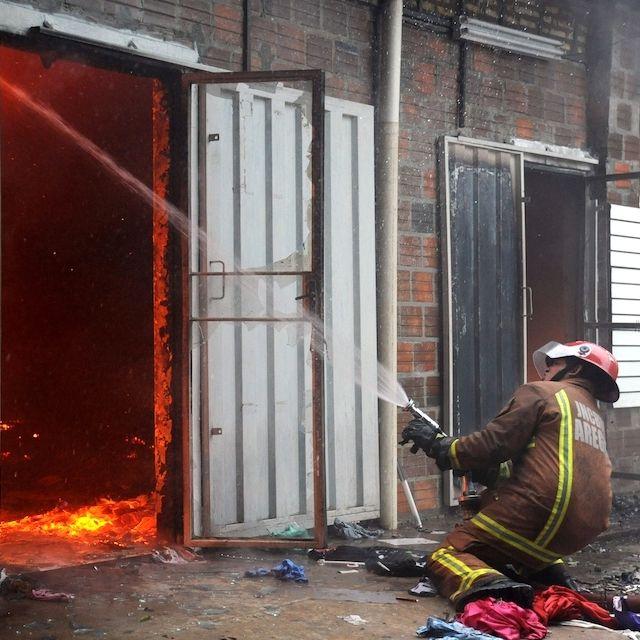 Un pompiere prova a spegnere un incendio in un mercato nel quartiere di San Lorenzo ad Asuncion, Paraguay