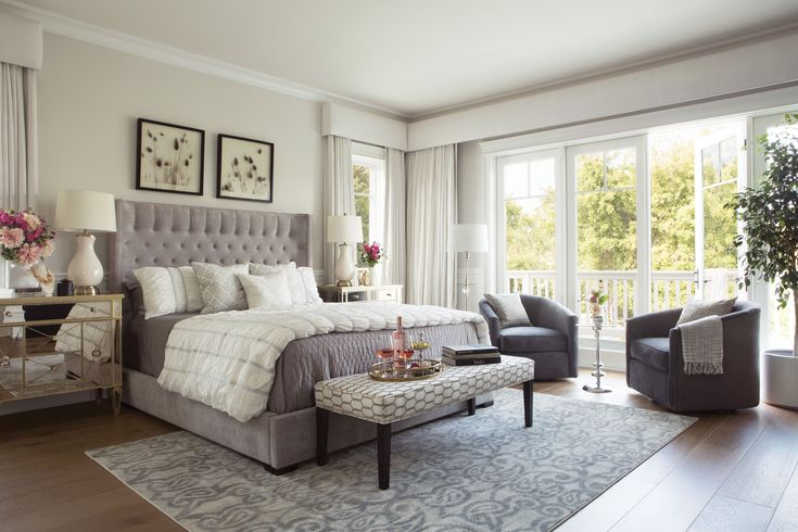 Turn your bedroom into a private retreat. With a grey, tufted, upholstered panel bed, a white and grey bench, a glass dresser with gold trim, and grey accent chairs, your space will certainly be calm and serene.