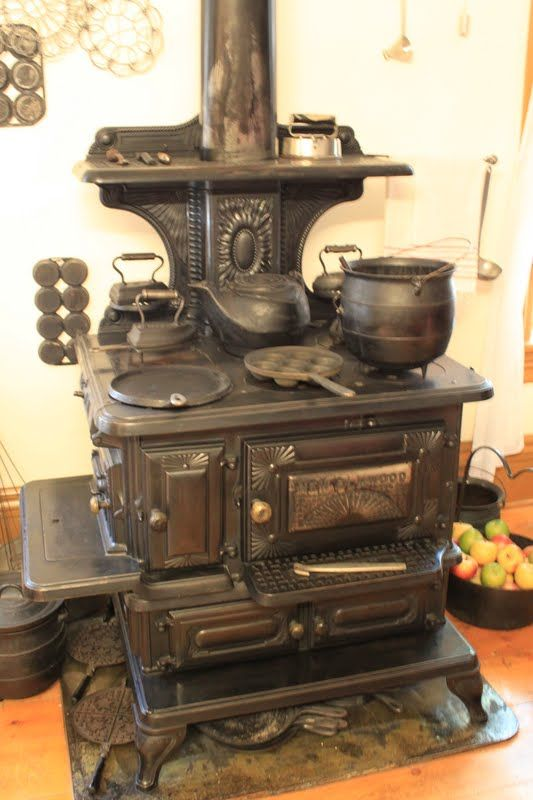 This is an old-fashioned wood burning cooking stove with all of the bells and whistles.  Notice all if the pots, kettles, and irons.  You can also see a type of frying pan and muffin pan on the front left and middle burners