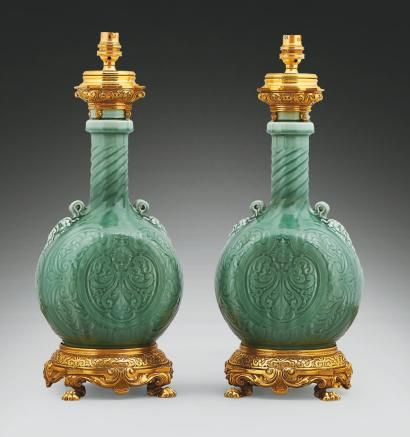 Theodore DECK (1823-1891) Pair of celadon ceramic lamps with flat, ovoid body, decorated on both sides by heads of Silenus in relief. Twisted neck effect. Decorated with foliage. Neck & base enclosed in ornate gilt bronze mounts Chinese pattern. Openwork base with four-claw feet.