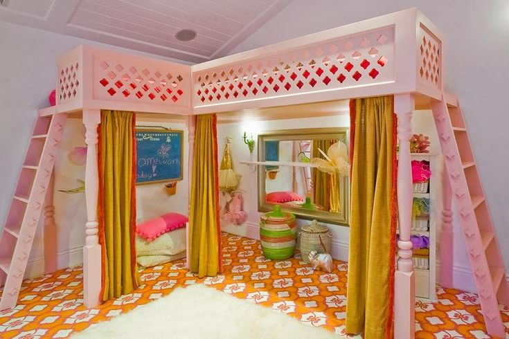 Fabulous girl's playroom features a pink Moroccan play loft lined with red and yellow curtains opening to a dress up area alongside a pink and orange rug.