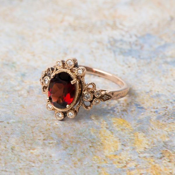 Gorgeous Garnet Engagement Rings | This garnet vintage-inspired ring is adorned on each edge with six brilliant-cut diamonds, creating beautiful symmetry. You'll feel like a queen with this find on your finger.