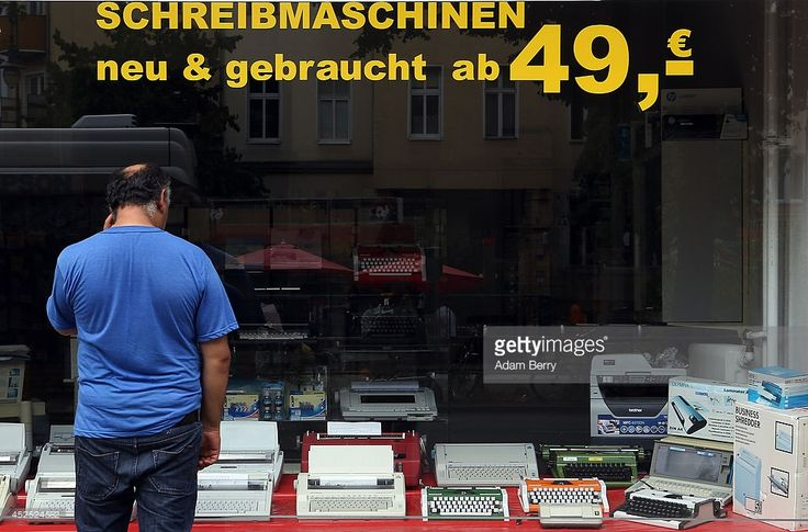 A pedestrian looks in a shop window at typewriters for sale on July 22, 2014 at the Arndt Hans Joachim Bueromaschinen office supply store in Berlin, Germany. Patrick Sensburg, the head of the German inquiry into the United States National Security Agency (NSA) spying scandal in which the U.S. agency is accused of having eavesdropped on German Chancellor Angela Merkel's mobile phone, told reporters that the investigation committee is considering using old-fashioned, non-electronic…