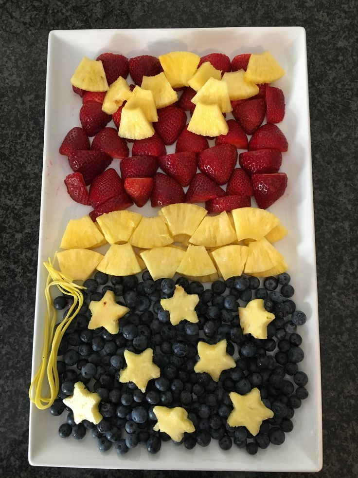 Wonder Woman fruit platter: strawberries, pineapple, and blueberries, with spaghetti dyed yellow for her golden lariat