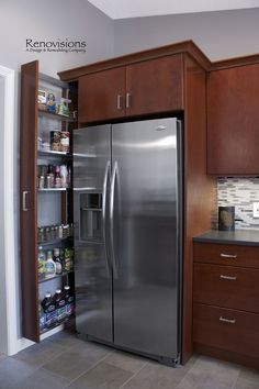 Contemporary kitchen remodel by Renovisions. Stainless steel appliances, glass mosaic backsplash tiles, stainless steel backsplash, Harlequin pattern, cement colored quartz countertop, Silestone countertop, suede finish countertop. Frameless cherry cabinets with a medium dark stain. Pull-out storage cabinet.