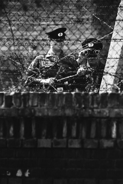 Two East German guards are seen through the barbed wire of the Berlin Wall looking back toward the western side. Note that the Vopo on the left is armed with a World War II-era PPSh-41 Russian submachine gun.