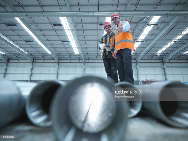 Stock Photo : Workers examining pipes in warehouse