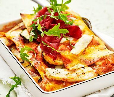 Denna tilltalande zucchinilasagne förgyller vilken vardag som helst. Zucchini är underbart gott att ugnsgratinera och i det här receptet är inget undantag. Pastasåsen får smak av en skvätt grädde innan den varvas med zucchini och halloumiost. Toppa med välsmakande bresaola och rucola innan servering.