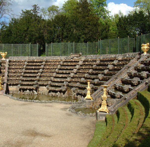 La salle de Bal  Aménagée par Le Nôtre entre 1680 et 1683, la salle de Bal s'appelle aussi bosquet des Rocailles, en raison des pierres de meulière et des coquillages rapportés des côtes africaines et malgaches sur lesquels l'eau ruisselle en cascade. Au centre, une « île » en marbre, aisément accessible, servait à la danse, art dans lequel s'illustrait Louis XIV. Les musiciens se tenaient au-dessus de la cascade et, en face, un amphithéâtre aux gradins recouverts de gazon permettait ...