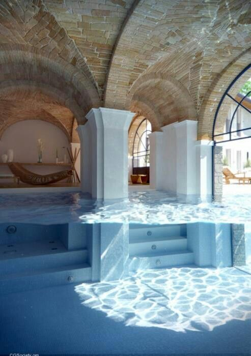 ok this is crazy a half indoor half outdoor swimming pool complete with arches steps