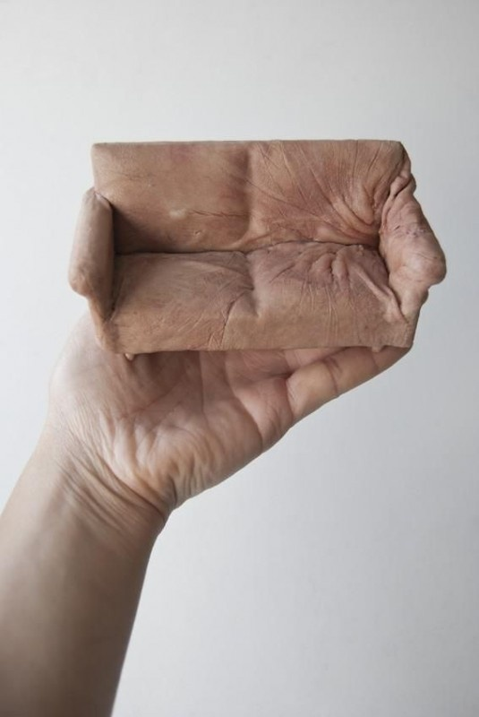 "In the unsettling sculpture series ""Handheld,"" small models of furniture appear to be made out of human skin. In actuality British artist Jessica Harrison created the sculptures using casts of her own hands."