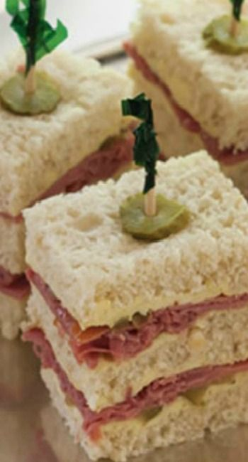 Corned Beef Tea Sandwiches with Mustard Butter    Traditionally, tea sandwiches are dainty little bites, but these triple-stack Corned Beef Tea Sandwiches, made with hearty oatmeal bread, are enough to make a meal.