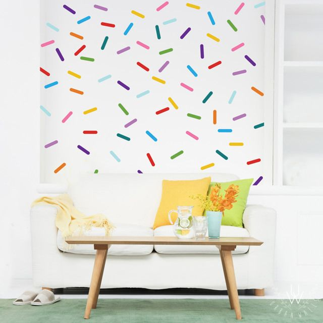 Small confetti rainbow colored wall decals in a variety of colors, evenly spaced as a pattern. Each sprinkle combines together on the white wall to make a wallpaper-like pattern of sprinkles. The colors include red, pink, blue, yellow, orange, lime green, turquoise, baby blue, violet, and purple.