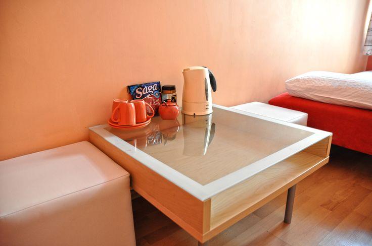 Stolik z wygodnymi pufami i wyposazeniem do zrobienia kawy i herbaty  http://www.rainbowapartments.pl/pokoj-czerwony/