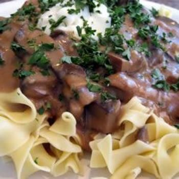 Portobello Mushroom Stroganoff - 3 tablespoons butter - 1 large onion, chopped - 3/4 pound portobello mushrooms, sliced - 1 1/2 cups vegetable broth - 1 1/2 cups sour cream - 3 tablespoons all-purpose flour - 1/4 cup chopped fresh parsley - 8 ounces dried egg noodles