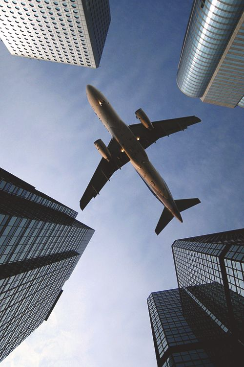 A commercial plane at the end of a tunnel of skyscrapers.