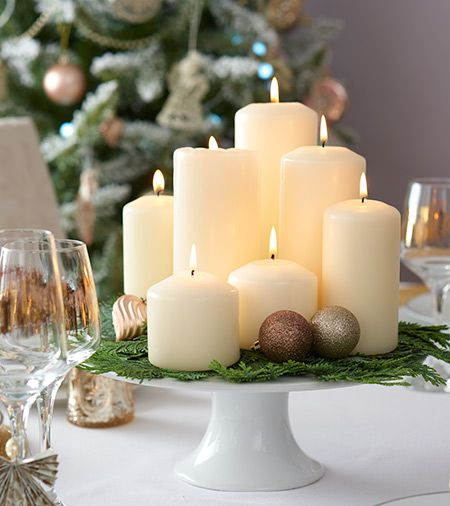 Make a candle display for your Christmas table centrepiece by grouping different-sized candles together and arranging them on a cake stand. Just add a few sprigs of fern and pine cones.