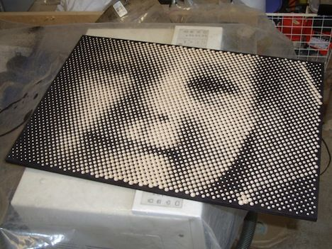 """The picture above is the result of a CNC router drilling holes of different depth and width with a conical bit on a piece of stained plywood. The bigger the hole, the less of the stained surface that shows and the lighter that """"pixel"""" is. It's a cool piece made by Finland-based artist Tomi and each piece takes about an hour to create."""