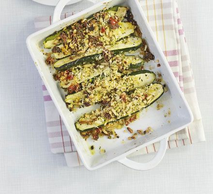 Pack courgettes with pine nuts, sundried tomatoes, breadcrumbs and herbs then oven bake for a healthy veggie main