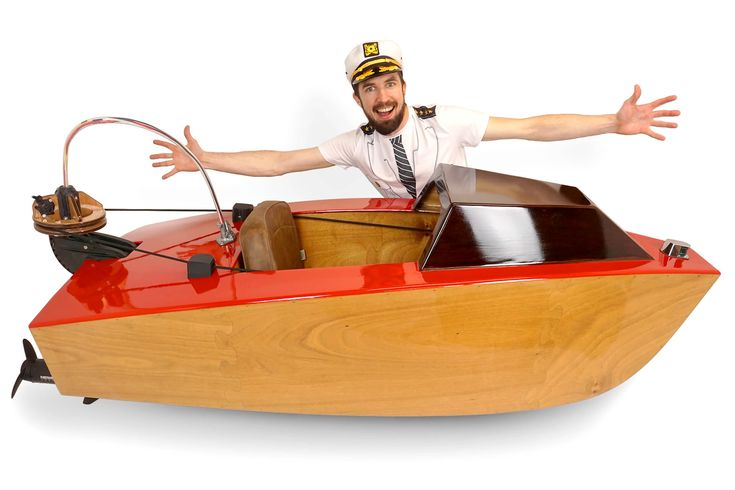 A hero shot of the laser cut mini boat with the creator behind it