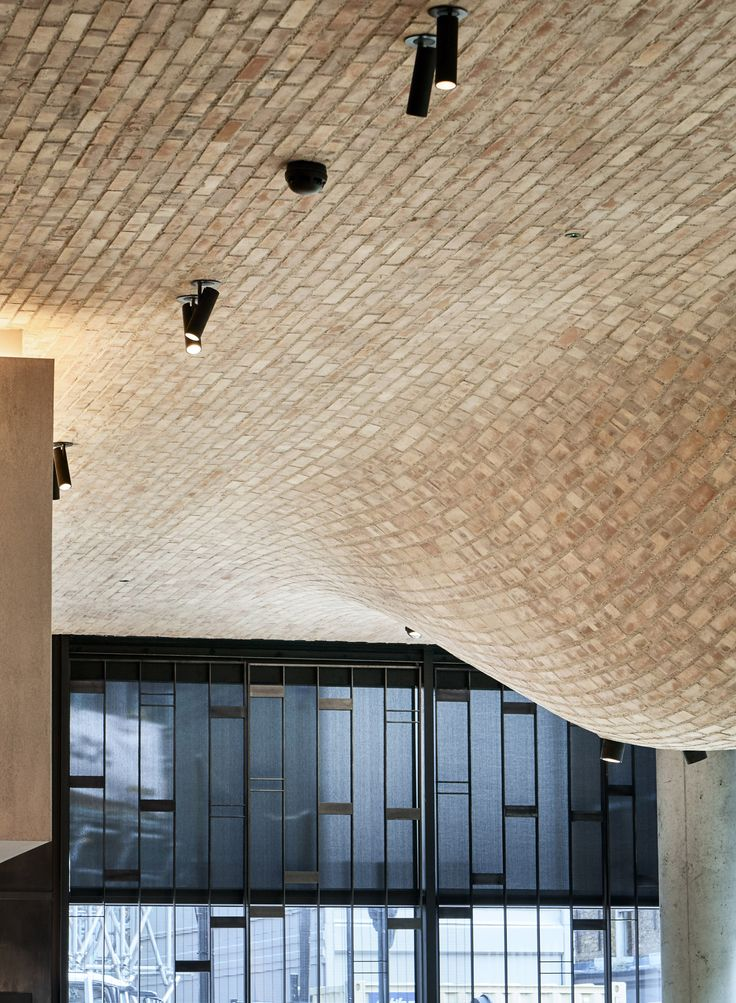 Hump-like protrusions extend down from the brick ceiling of this London restaurant by Andy Martin Architects, referencing the domed interior of pizza ovens