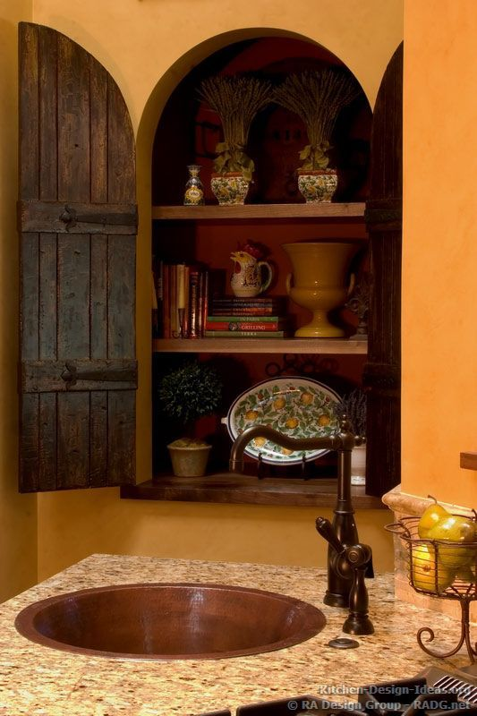 An arched wall niche with old wood doors and antique hinges.: