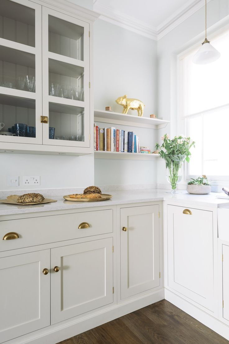 Cool and calm, this beautifully bright kitchen felt elegant and classic with deVOL Shaker cupboards painted in a bespoke soft grey, brass handles and Ibiza Snow Silestone worktops